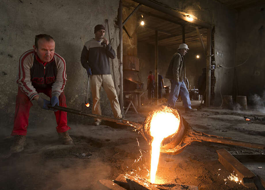 Workers pour melted metal into a cast of manhole covers after the destruction of weapons held illegally in Kosovo in a metal foundry near the town of Ferizaj in Kosovo on Tuesday, Dec. 2, 2014. . Kosovo authorities destroyed over 2,000 small arms and rifles on Tuesday as part of an ongoing effort to increase security in the Balkan country. (AP Photo/Visar Kryeziu)