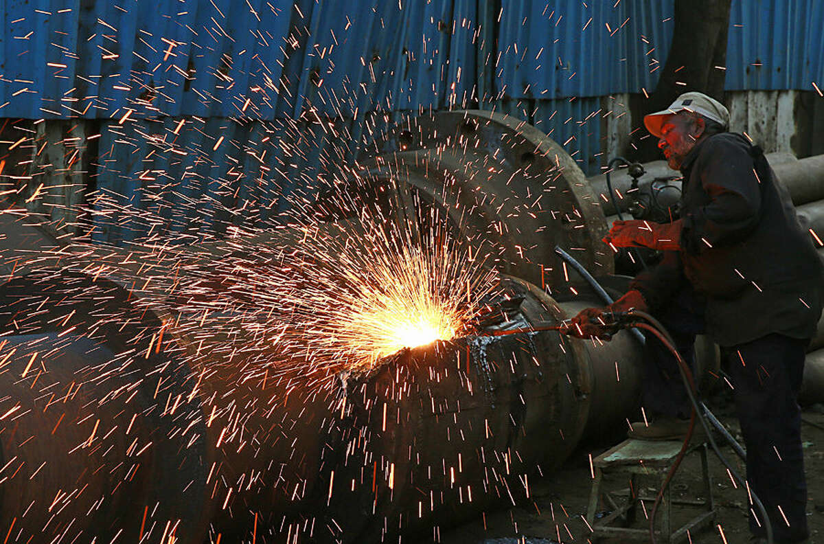 An Indian worker works at an iron and steel scrap workshop at an industrial area on Reay Road in Mumbai, India, Monday, Dec 1, 2014. Mumbai is also known as the financial capital of India. (AP Photo/Rafiq Maqbool)