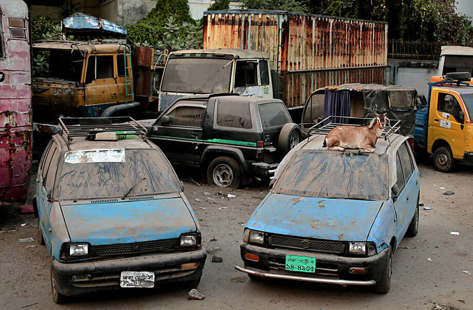 A goat sits on top of a car at a vehicle dumping yard in Dhaka, Bangladesh, Tuesday, Dec. 2, 2014. (AP Photo/A.M. Ahad)