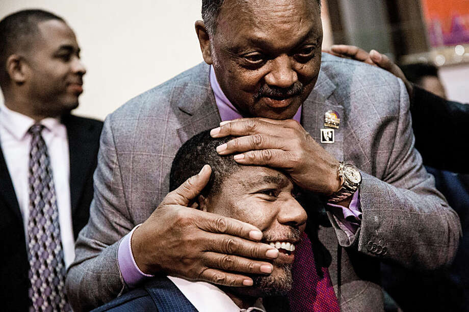 Rev. Jesse L. Jackson, top, playfully hugs the head of Rev. Paul Stoot Sr., after addressing a crowd of community members while on a visit to Seattle for a series of meetings with community, business and religious leaders, Sunday, Nov. 30, 2014, at Mount Zion Baptist Church in Seattle. Earlier this year, Jackson highlighted the longstanding pattern of exclusion of women and minorities in high-tech fields, from corporate boards and executives to rank-and-file employees. (AP Photo/seattlepi.com, Jordan Stead)