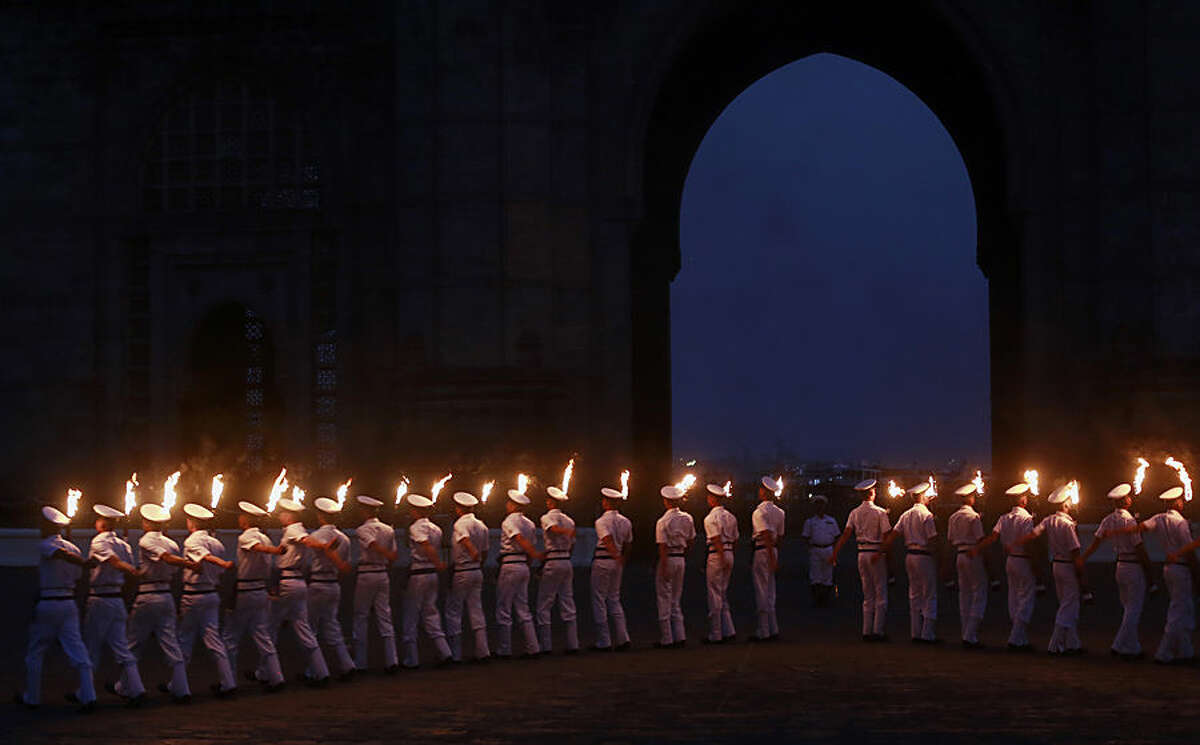 Indian navy personnel hold torches as they perform a drill during Naval Day celebrations at the Arabian Sea in Mumbai, India, Tuesday, Dec. 2, 2014. Navy day is celebrated on Dec. 4. (AP Photo/Rafiq Maqbool)