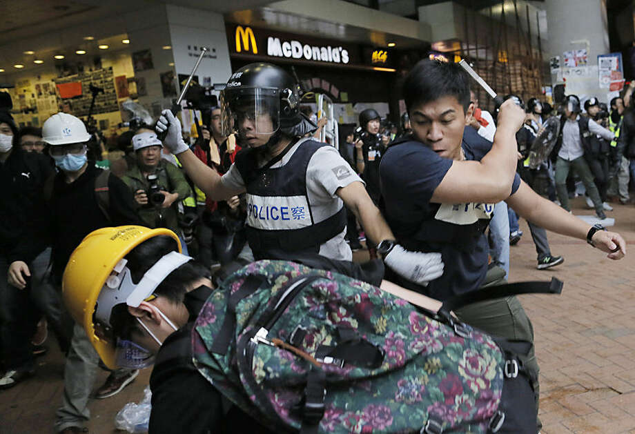 Police officers beat up protesters as they try to disperse them outside government headquarters in Hong Kong Monday, Dec. 1, 2014. Pro-democracy protesters clashed with police as they tried to surround Hong Kong government headquarters late Sunday, stepping up their movement for genuine democratic reforms after camping out on the city's streets for more than two months. (AP Photo/Vincent Yu)