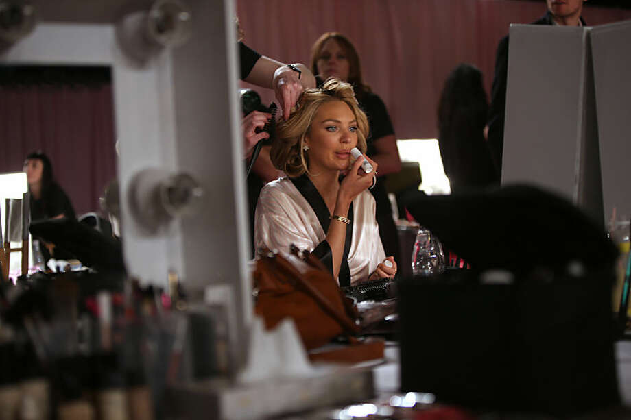 Model Candice Swanepoel is made up backstage at the Victoria's Secret fashion show in London, Tuesday, Dec. 2, 2014. (Photo by Joel Ryan/Invision/AP)