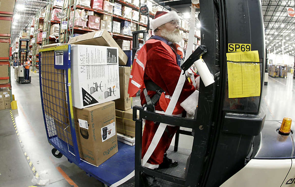 Glenn Wright, dressed in a Santa Claus costume, moves items at the Amazon fulfillment center on Monday, Dec. 1, 2014, in Lebanon, Tenn. Retailers rolled out discounts and free shipping deals on Cyber Monday, with millions of Americans expected to log on and shop on their work computers, laptops and tablets after the busy holiday shopping weekend. (AP Photo/Mark Humphrey)