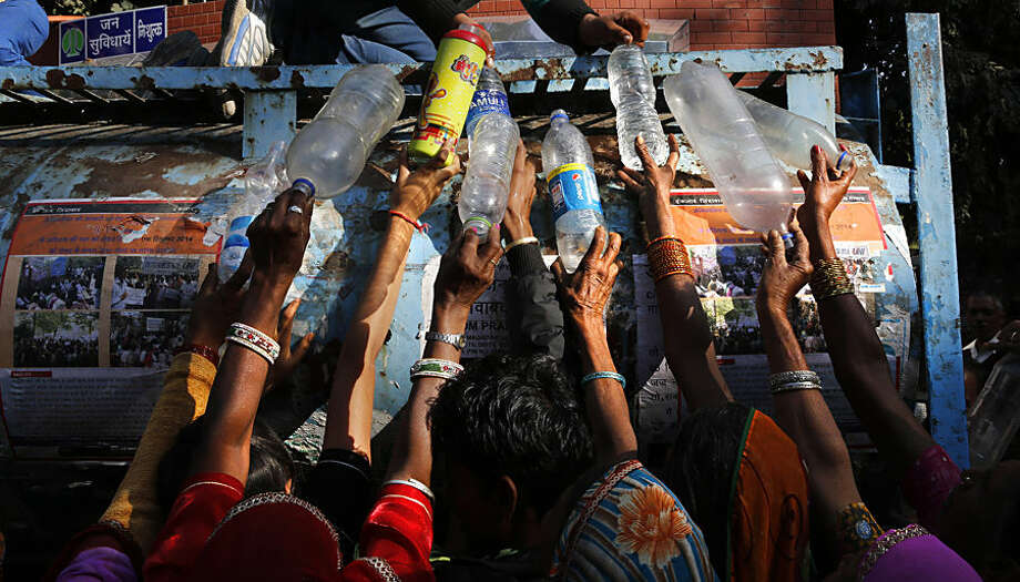 Indian women protesters from the Indian state fill their bottles with drinking water as they participate in a rally in New Delhi, India, Tuesday, Dec. 2, 2014. Thousands of workers, farmers, pensioners, slum dwellers and other underprivileged people gathered near the Indian parliament raising various economic and social rights including pension, food, employment and healthcare among others. (AP Photo/Manish Swarup)