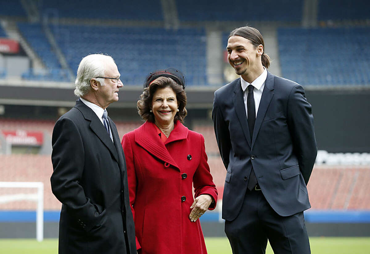 Sweden's King Carl XVI Gustaf, left, and Queen Silvia talk to Swedish soccer player Zlatan Ibrahimovic, right, during their visit of the Paris Saint Germain foundation at the Parc des Princes stadium, Tuesday, Dec. 2, 2014 in Paris. The Swedish royal couple is on a three-day state visit to France. (AP Photo/Yoan Valat, Pool)