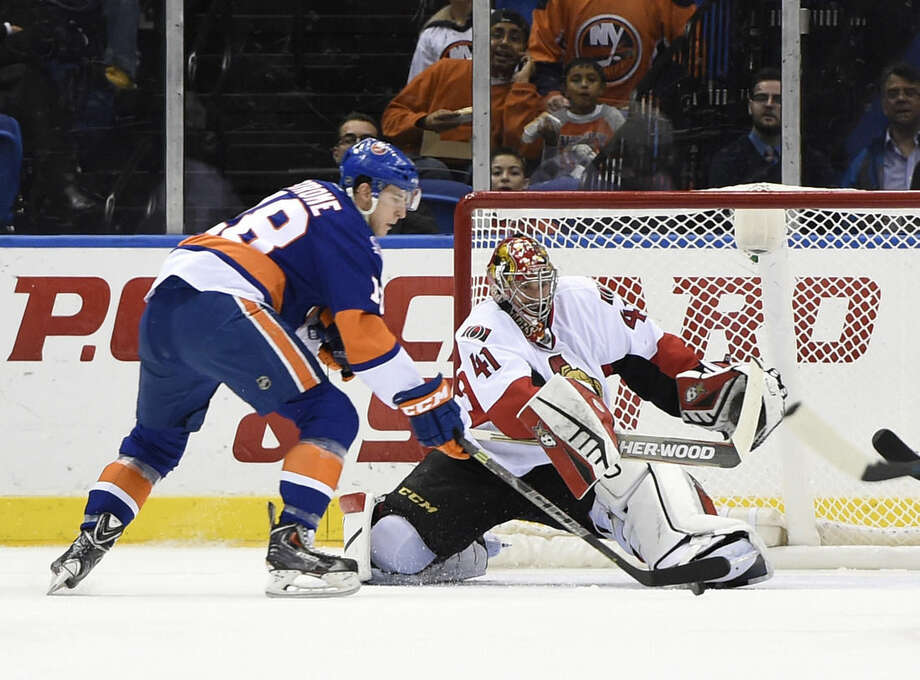 Ottawa Senators goalie Craig Anderson (41) stops a shot on goal by New York Islanders center Ryan Strome (18) in the first period of an NHL hockey game at Nassau Coliseum on Tuesday, Dec. 2, 2014, in Uniondale, N.Y. (AP Photo/Kathy Kmonicek)