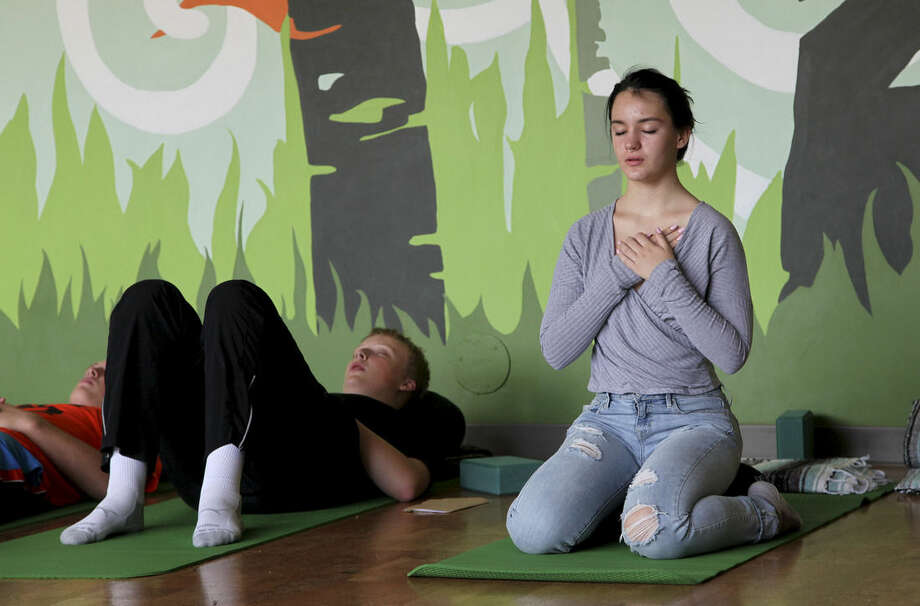 In this Oct. 1, 2014 photo, Nora Pearson, right, practices mindful breathing during the Mindful Studies class at Wilson High School in Portland, Ore. The year-long course is one of a growing number of programs that are incorporating mindfulness, yoga and meditation into school curriculums to bring socio-emotional benefits to students. (AP Photo/Gosia Wozniacka)
