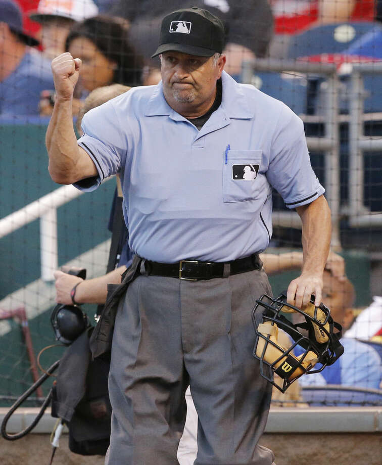 FILE - This june 5, 2014, file photo shows umpire Dale Scott calling out St. Louis Cardinals' Yadier Molina after a play review in the fifth inning of a baseball game against the Kansas City Royals at Kauffman Stadium in Kansas City, Mo. Major League Baseball umpire Dale Scott says he is gay. The 55-year-old umpire tells the website outsports.com that he married Michael Rausch in November 2013. (AP Photo/Orlin Wagner, File)