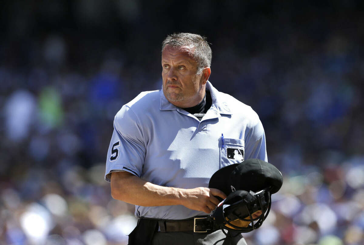 FILE - This Aug. 7, 2013, file photo shows Major League Baseball umpire Dale Scott preparing to return to action after being injured in the second inning of a baseball game between the Mariners and Toronto Blue Jays in Seattle. Dale Scott says he is gay. The 55-year-old umpire who has worked three World Series tells the website outsports.com that he married his longtime companion in November 2013. (AP Photo/Elaine Thompson, File)