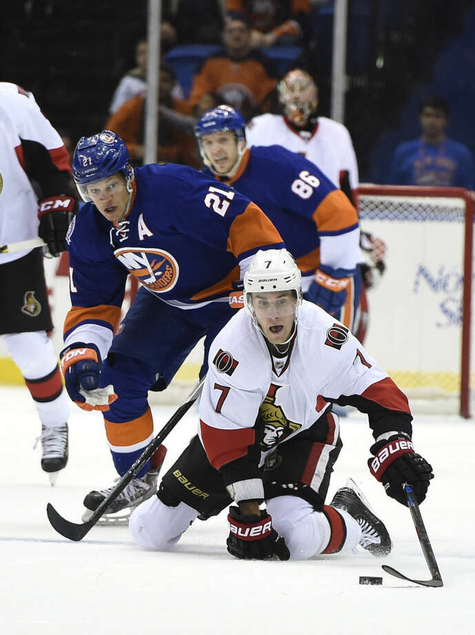 Ottawa Senators center Kyle Turris (7) dives to the ice to control the puck against New York Islanders right wing Kyle Okposo (21) in the first period of an NHL hockey game at Nassau Coliseum on Tuesday, Dec. 2, 2014, in Uniondale, N.Y. (AP Photo/Kathy Kmonicek)