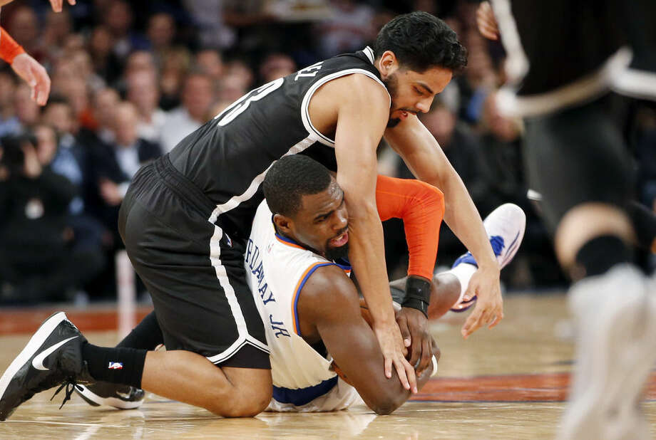 Brooklyn Nets guard Jorge Gutierrez (13) and New York Knicks guard Tim Hardaway Jr. (5) scramble for a loose ball in the first half of an NBA basketball game at Madison Square Garden in New York, Tuesday, Dec. 2, 2014. (AP Photo/Kathy Willens)