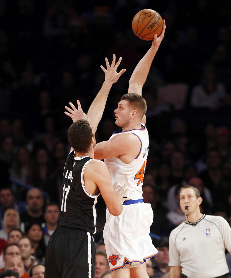 New York Knicks center Cole Aldrich (45) shoots over Brooklyn Nets center Brook Lopez (11) in the first half of an NBA basketball game at Madison Square Garden in New York, Tuesday, Dec. 2, 2014. (AP Photo/Kathy Willens)