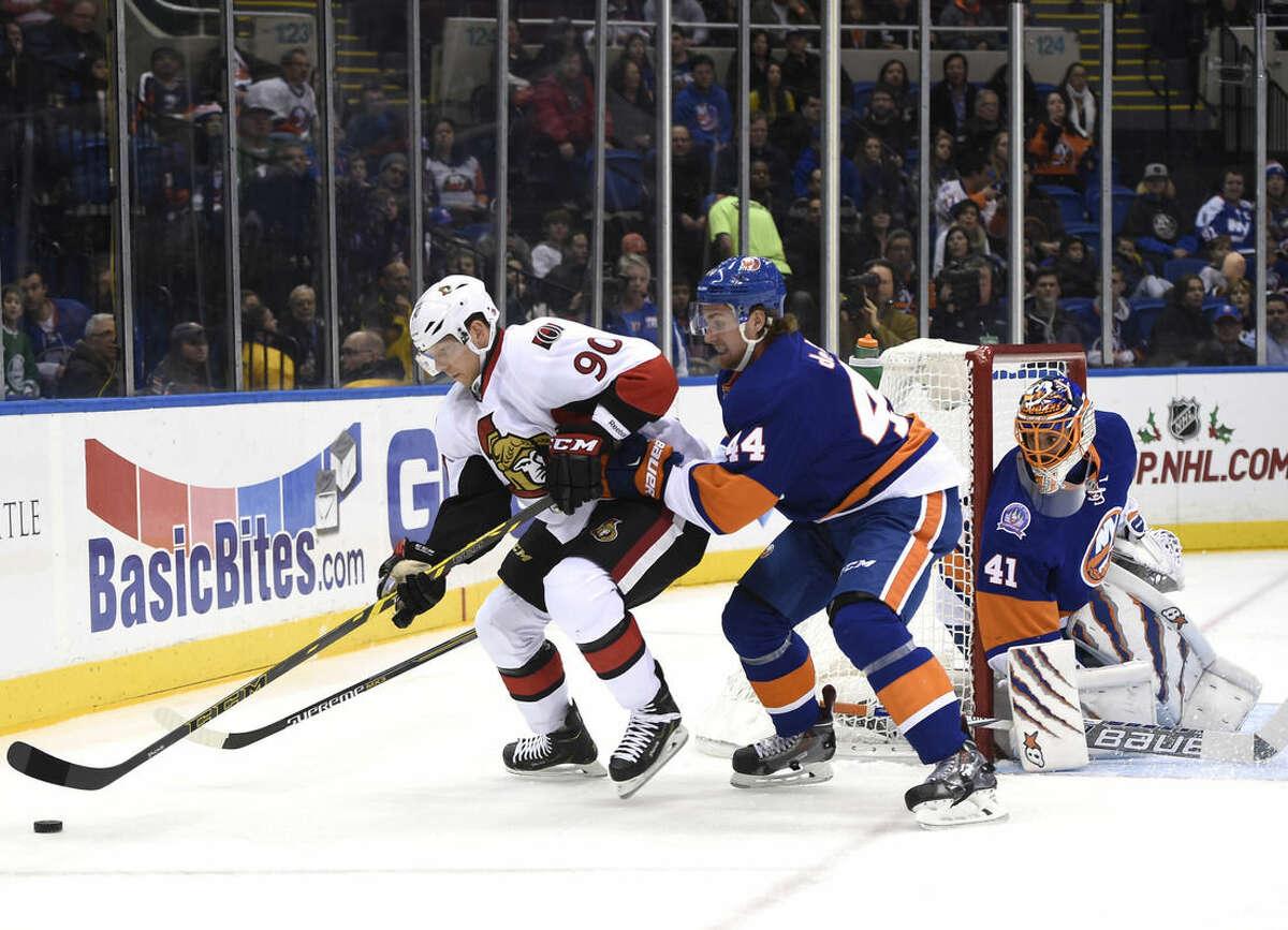 Ottawa Senators right wing Alex Chiasson (90) controls the puck against New York Islanders defenseman Calvin de Haan (44) as goalie Jaroslav Halak (41) defends the net in the first period of an NHL hockey game at Nassau Coliseum on Tuesday, Dec. 2, 2014, in Uniondale, N.Y. (AP Photo/Kathy Kmonicek)