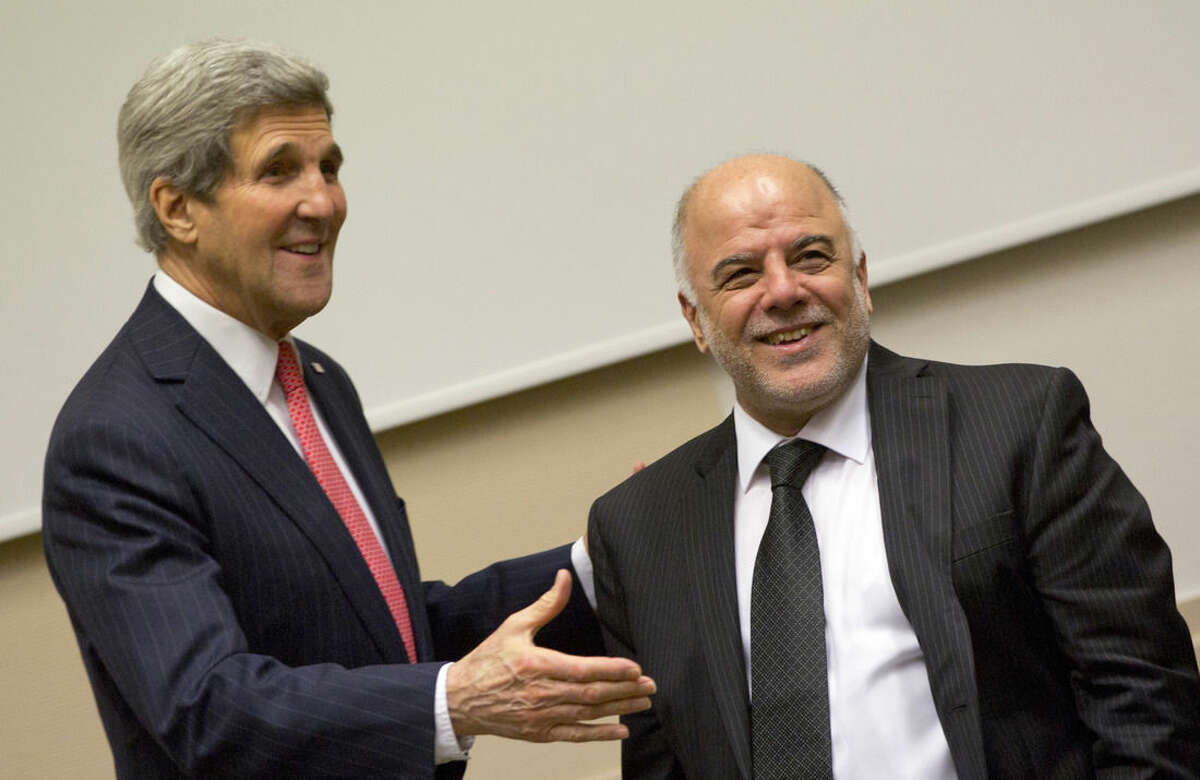 U.S. Secretary of State John Kerry, left, reaches out to shake hands with Iraqi Prime Minister Haider al-Abadi during a meeting prior to a round table meeting of the global coalition to counter the Islamic State militant group at NATO headquarters in Brussels on Wednesday, Dec. 3, 2014. Kerry opened on Wednesday a high-level meeting at NATO Headquarters of countries participating in the campaign against the Islamic State organization to assess what's been accomplished and what remains to be done. (AP Photo/Virginia Mayo, Pool)