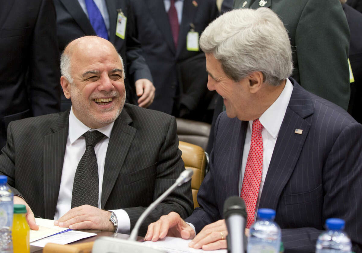 U.S. Secretary of State John Kerry, right, and Iraqi Prime Minister Haider al-Abadi, left, speak during a round table meeting of the global coalition to counter the Islamic State militant group at NATO headquarters in Brussels on Wednesday, Dec. 3, 2014. U.S. Secretary of State John Kerry opened on Wednesday a high-level meeting at NATO headquarters of countries participating in the campaign against the Islamic State organization to assess what's been accomplished and what remains to be done. (AP Photo/Virginia Mayo)