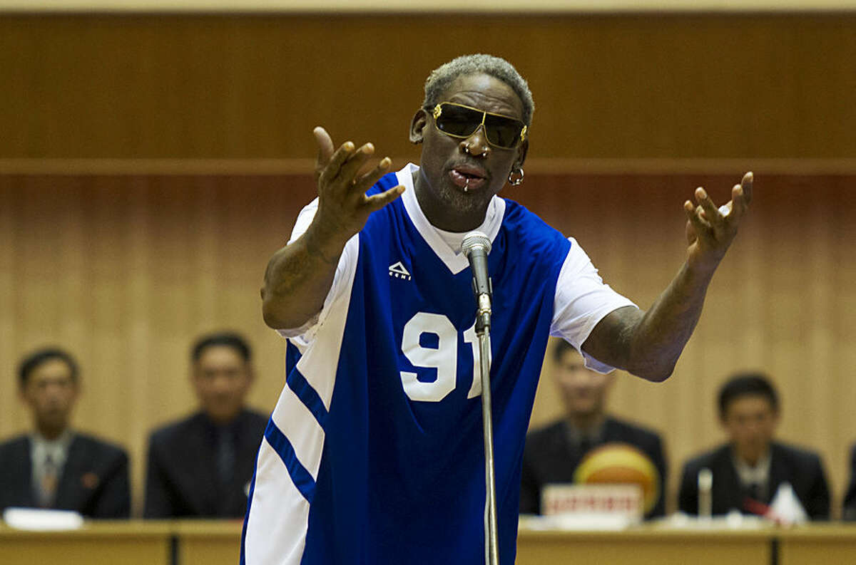 FOR USE AS DESIRED, YEAR END PHOTOS - FILE - Dennis Rodman sings Happy Birthday to North Korean leader Kim Jong Un, seated above in the stands, before an exhibition basketball game at an indoor stadium in Pyongyang, North Korea on Wednesday, Jan. 8, 2014. (AP Photo/Kim Kwang Hyon, File)