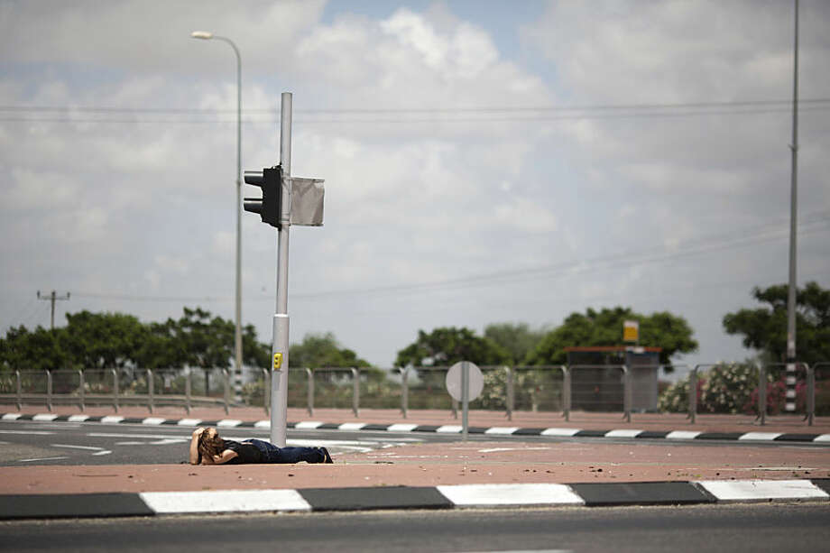 FOR USE AS DESIRED, YEAR END PHOTOS - FILE - An Israeli woman takes cover as siren alarming sounds warning of rocket attacks by Palestinians militants from Gaza Strip in Ashkelon, southern Israel, Monday, July 14, 2014. (AP Photo/Ariel Schalit, File)