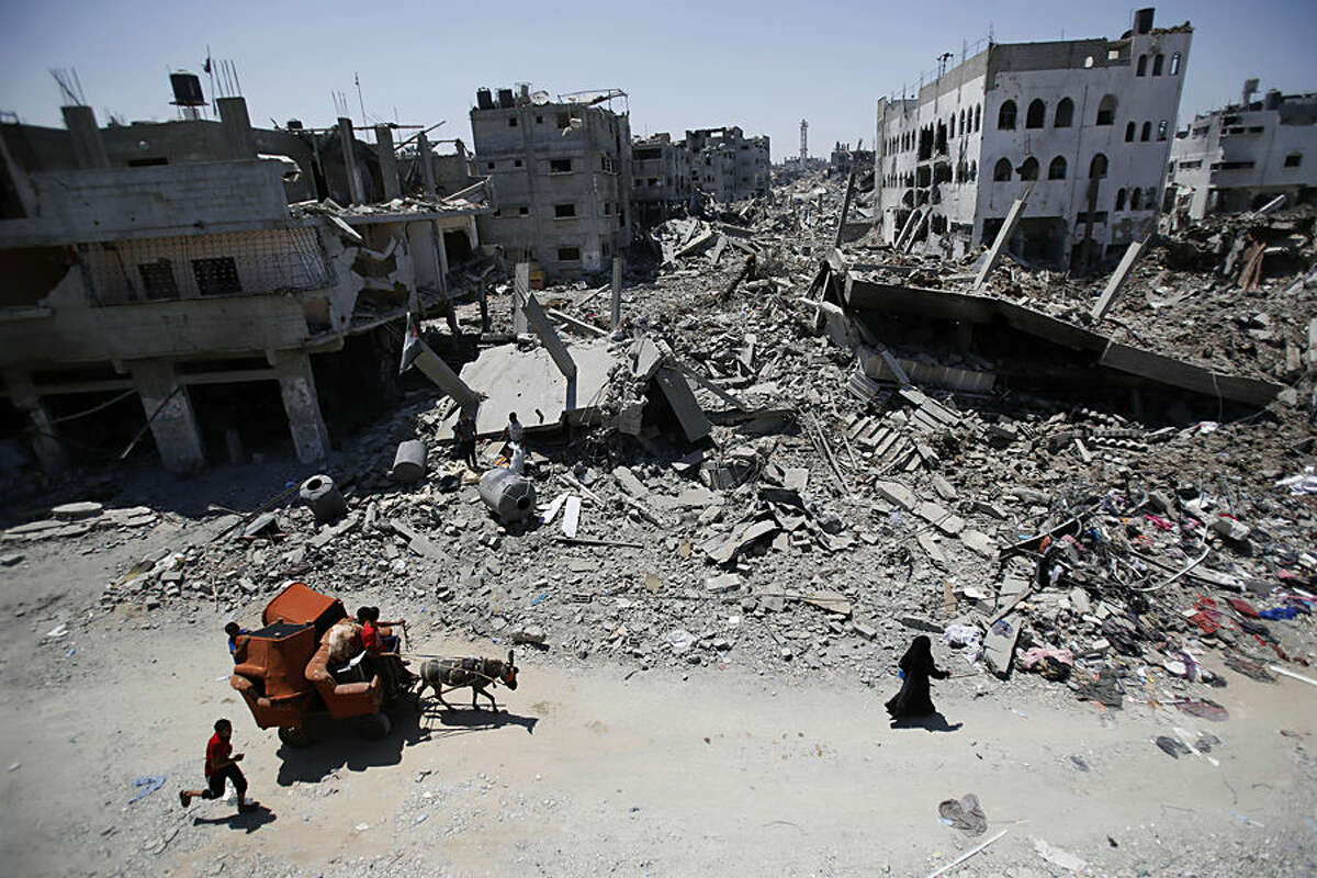 FOR USE AS DESIRED, YEAR END PHOTOS - FILE - Palestinians carry their belongings through the heavily bombed Gaza City neighborhood of Shijaiyah, close to the Israeli border, Friday, Aug. 1, 2014. (AP Photo/Hatem Moussa, File)