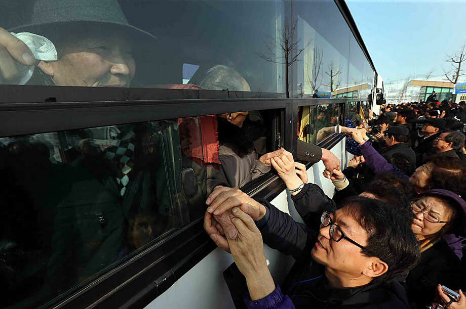 FOR USE AS DESIRED, YEAR END PHOTOS - FILE - South Koreans hold their North Korean relative's hands on a bus after the Separated Family Reunion Meeting at Diamond Mountain in North Korea, Tuesday, Feb. 25, 2014. The first reunions of North and South Koreans in more than three years have were held in North Korea. The final group of Koreans to participate in reunions ends Tuesday. (AP Photo/Yonhap, Lee Ji-eun, File) KOREA OUT