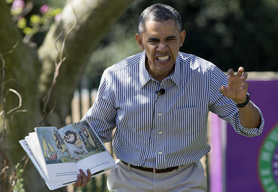 "FOR USE AS DESIRED, YEAR END PHOTOS - FILE - President Barack Obama makes a face as he reads ""Where the Wild Things Are"" by Maurice Sendak, during the White House Easter Egg Roll on the South Lawn of the White House is Washington, Monday, April 21, 2014. Thousands of children gathered at the White House for the annual Easter Egg Roll. This year's event features live music, cooking stations, storytelling, and of course, some Easter egg rolling. (AP Photo/Carolyn Kaster, File)"
