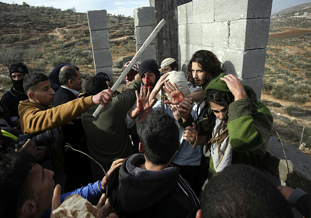 FOR USE AS DESIRED, YEAR END PHOTOS - FILE - Palestinians hit Israeli settlers while others try to stop them before a group of settlers were detained by Palestinian villagers in a building under construction near the West Bank village of Qusra, southeast of the city of Nablus, Tuesday, Jan. 7, 2014. Palestinians held more than a dozen Israeli settlers for about two hours in retaliation for the latest in a string of settler attacks on villages in the area, witnesses said. The military said the chain of events apparently began after Israeli authorities removed an illegally built structure in Esh Kodesh, a rogue Israeli settlement in the area. In recent years, militant settlers have often responded to any attempts by the Israeli military to remove parts of dozens of rogue settlements, or outposts, by attacking Palestinians and their property. The tactic, begun in 2008, is known as
