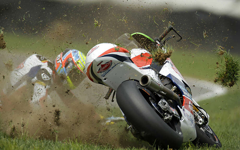 FOR USE AS DESIRED, YEAR END PHOTOS - FILE - Xavier Simeon, of Belgium, crashes during Indianapolis Moto 2 motorcycle race at the Indianapolis Motor Speedway in Indianapolis, Sunday, Aug. 10, 2014. (AP Photo/Michael Conroy, File)