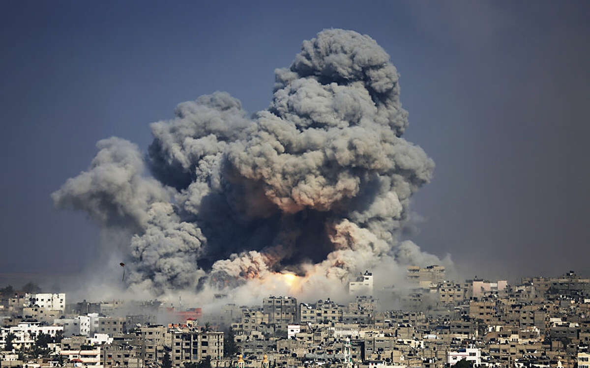 FOR USE AS DESIRED, YEAR END PHOTOS - FILE - Smoke and fire from the explosion of an Israeli strike rise over Gaza City, Tuesday, July 29, 2014. Israel escalated its military campaign against Hamas striking symbols of the group's control in Gaza and firing tank shells that shut down the strip's only power plant in the heaviest bombardment in the fighting so far. (AP Photo/Hatem Moussa, File)