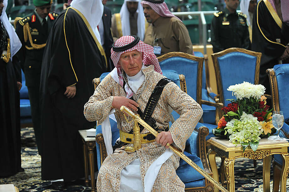 "FOR USE AS DESIRED, YEAR END PHOTOS - FILE - Britain's Prince Charles wears a traditional Saudi uniform as he attends the traditional Saudi dancing best known as ""Arda,"" performed during Janadriya culture festival at Der'iya in Riyadh, Tuesday, Feb. 18, 2014. (AP Photo/Fayez Nureldine, File Pool)"