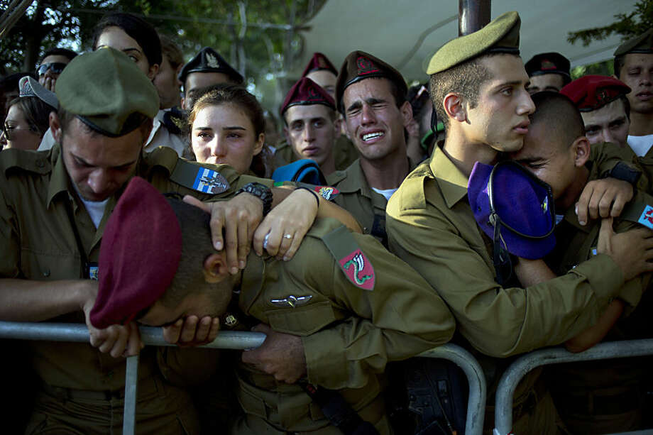 "FOR USE AS DESIRED, YEAR END PHOTOS - FILE - Israeli soldiers mourn over the grave of Sergeant Sagi Erez, an infantry soldier training to be a squad commander, during his funeral at the military cemetery in Haifa, northern Israel, Tuesday, July 29, 2014. Erez, 19, was killed in combat after Gaza militants used a tunnel to sneak into Israel. Israeli Prime Minister Benjamin Netanyahu said Monday that Israel must be ready for a ""prolonged"" military operation in the Gaza Strip. (AP Photo/Ariel Schalit, File)"