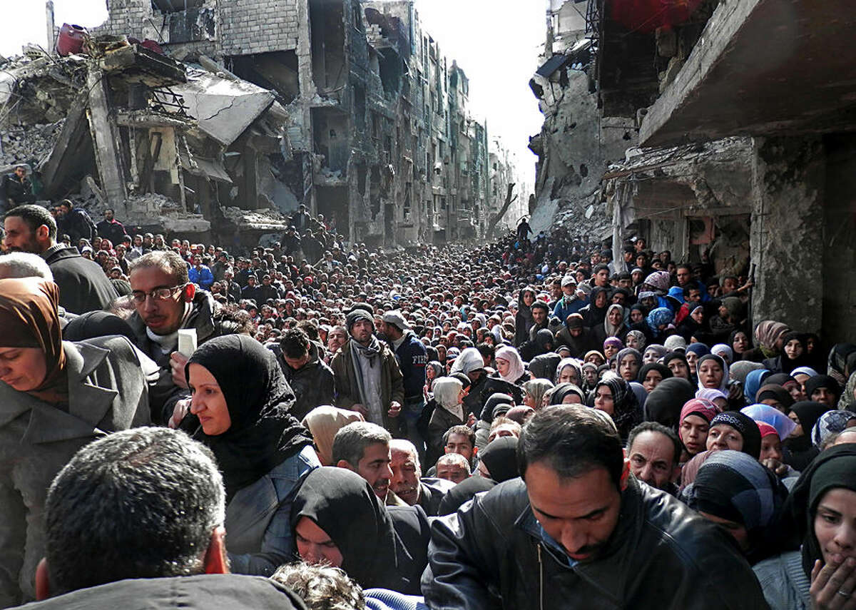 FOR USE AS DESIRED, YEAR END PHOTOS - FILE - This picture taken on Jan. 31, 2014, and released by the UNRWA, shows residents of the besieged Palestinian camp of Yarmouk, queuing to receive food supplies, in Damascus, Syria. A United Nations official called on warring sides in Syria to allow aid workers to resume distribution of food and medicine in a besieged Palestinian district of Damascus. The call comes as U.N. Secretary General Ban Ki-Moon urged Syrian government to authorize more humanitarian staff to work inside the country, devastated by its 3-year-old conflict. (AP Photo/UNRWA, File)