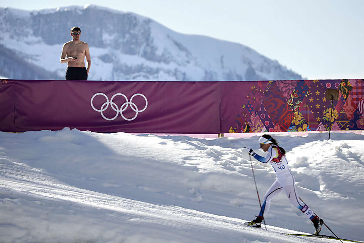 FOR USE AS DESIRED, YEAR END PHOTOS - FILE - A shirtless spectator watches Sweden's Charlotte Kalla compete during the women's 10K classical style cross-country race at the 2014 Winter Olympics, Thursday, Feb. 13, 2014, in Krasnaya Polyana, Russia. Kalla won the silver medal. (AP Photo/Jae C. Hong, File)
