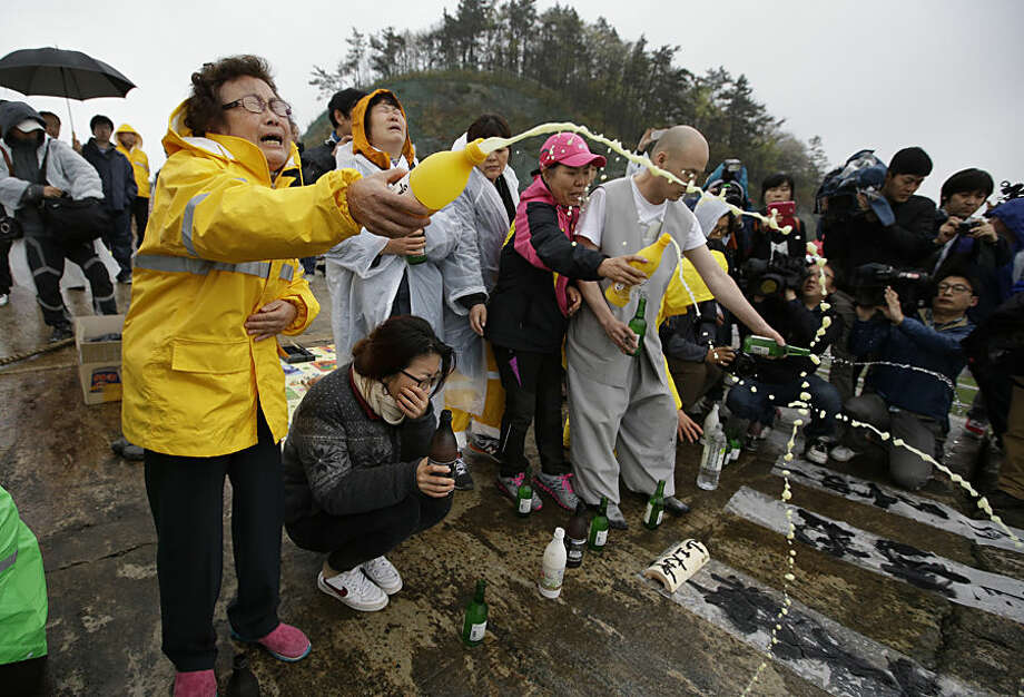 FOR USE AS DESIRED, YEAR END PHOTOS - FILE - A Buddhist monk and relatives of passengers aboard a sunken ferry spray alcohols during a Buddhist ceremony to pray for speedy rescue and their safety at a port in Jindo, south of Seoul, South Korea, Friday, April 18, 2014. The ferry flipped onto its side and filled with water off the southern coast of South Korea. (AP Photo/Lee Jin-man, File)