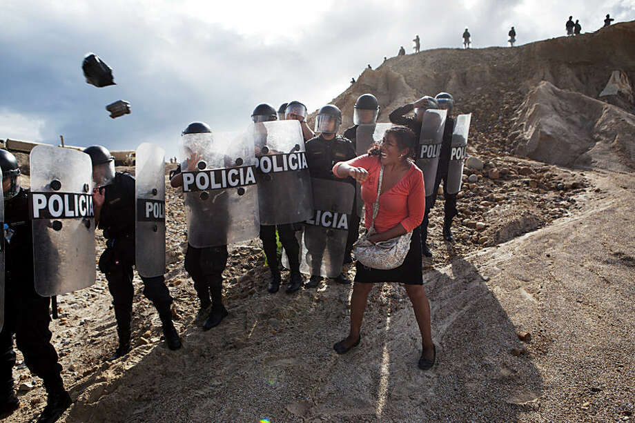 FOR USE AS DESIRED, YEAR END PHOTOS - FILE - A woman throws a rock and a bag at riot policemen who block her way home in Huepetuhe district in Peru's Madre de Dios region in Peru, Monday, April 28, 2014. Soldiers, police and marines have begun destroying illegal gold mining machinery in Peru's southeastern jungle region of Madre de Dios. Authorities began enforcing a ban on illegal mining in the Huepetuhe district. Before the deadline, miners clashed with police while intermittently blocking traffic on the Interoceanic Highway that links the Pacific with Brazil. (AP Photo/Rodrigo Abd, File)