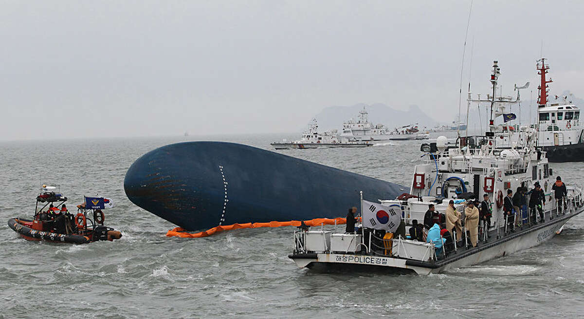 FOR USE AS DESIRED, YEAR END PHOTOS - FILE - South Korean Coast Guard officers try to rescue missing passengers from a sunken ferry in the water off the southern coast near Jindo, South Korea, Thursday, April 17, 2014. (AP Photo/Ahn Young-joon, File)