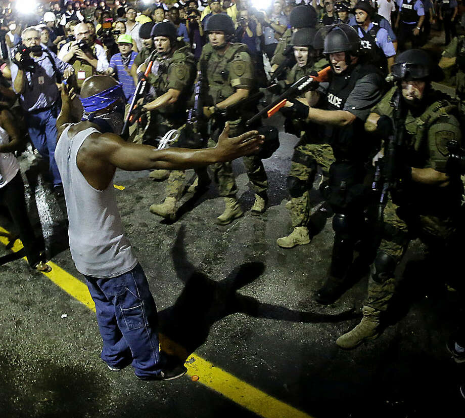 FOR USE AS DESIRED, YEAR END PHOTOS - FILE - Police arrest a man as they disperse a protest in Ferguson, Mo., early Wednesday, Aug. 20, 2014. On Saturday, Aug. 9, a white police officer fatally shot unarmed 18-year-old Michael Brown, who was black, in the St. Louis suburb. (AP Photo/Charlie Riedel, File)