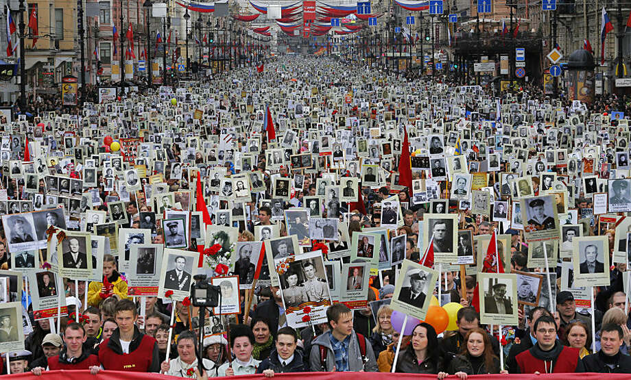 FOR USE AS DESIRED, YEAR END PHOTOS - FILE - Local residents carry portraits of their ancestors, participants in World War Two as they celebrate Victory Day in St.Petersburg, Russia, Friday, May 9, 2014. About 30,000 people walked in central streets in a march named 'Immortal regiment' while carrying portraits their relatives who fought in World War Two. Victory Day, marking the defeat of Nazi Germany, is Russia's most important secular holiday , celebrated on May 9. (AP Photo / Dmitry Lovetsky, File)
