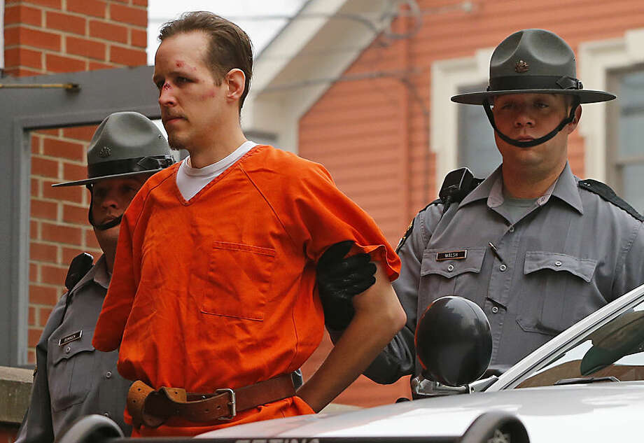 FOR USE AS DESIRED, YEAR END PHOTOS - FILE - Eric Frein is escorted by police into the Pike County Courthouse for his arraignment in Milford, Pa., Friday Oct. 31, 2014. Frein was captured seven weeks after police say he killed a Pennsylvania State trooper in an ambush outside a barracks in northeastern Pennsylvania. (AP Photo/Rich Schultz, File)