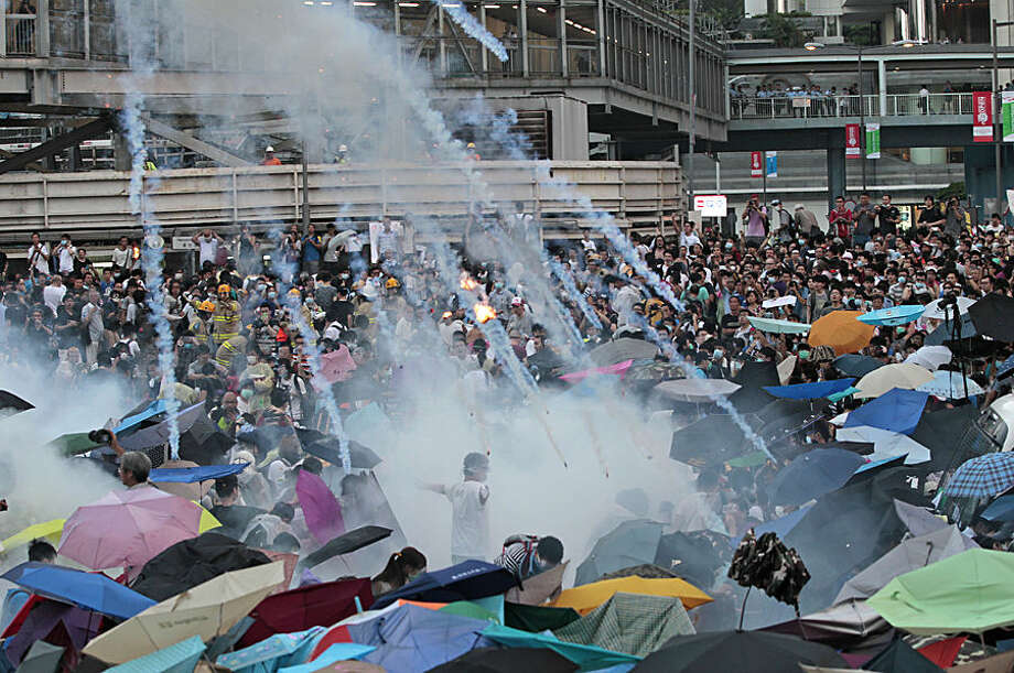 FOR USE AS DESIRED, YEAR END PHOTOS - FILE - Riot police launch tear gas into the crowd as thousands of protesters surround the government headquarters in Hong Kong Sunday, Sept. 28, 2014. Hong Kong police used tear gas and warned of further measures as they tried to clear thousands of pro-democracy protesters gathered outside government headquarters in a challenge to Beijing over its decision to restrict democratic reforms for the city. (AP Photo/Wally Santana, File)