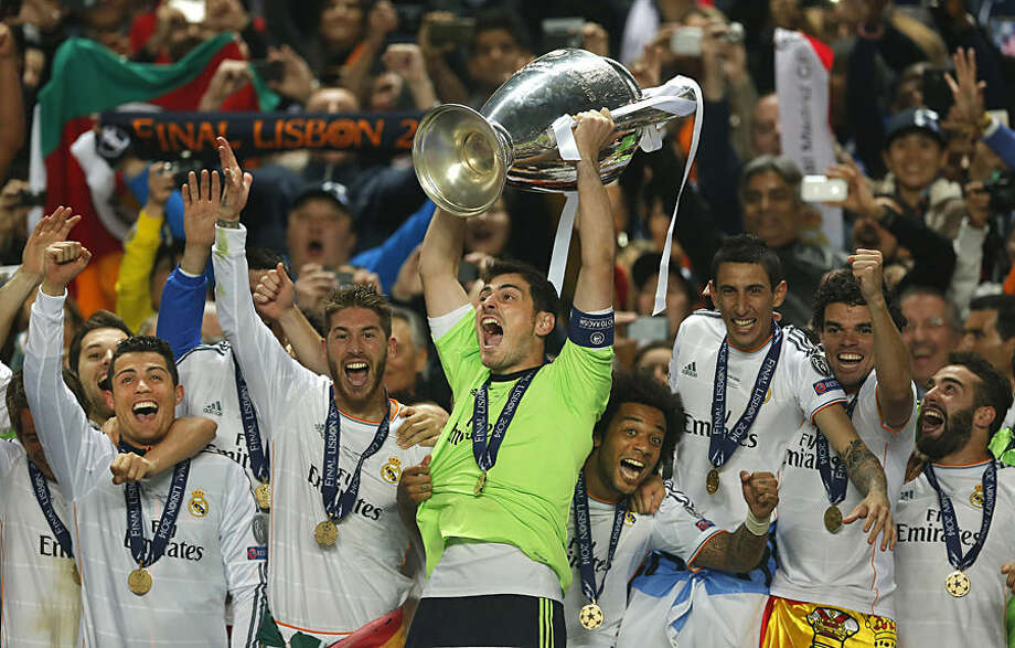 FOR USE AS DESIRED, YEAR END PHOTOS - FILE - Real goalkeeper Iker Casillas, center, lifts the Champion League trophy, as he and teammates, celebrate winning the Champion League title, against Atletico Madrid, in Lisbon, Portugal, Saturday, May 24, 2014. (AP Photo/Andres Kudacki, File)