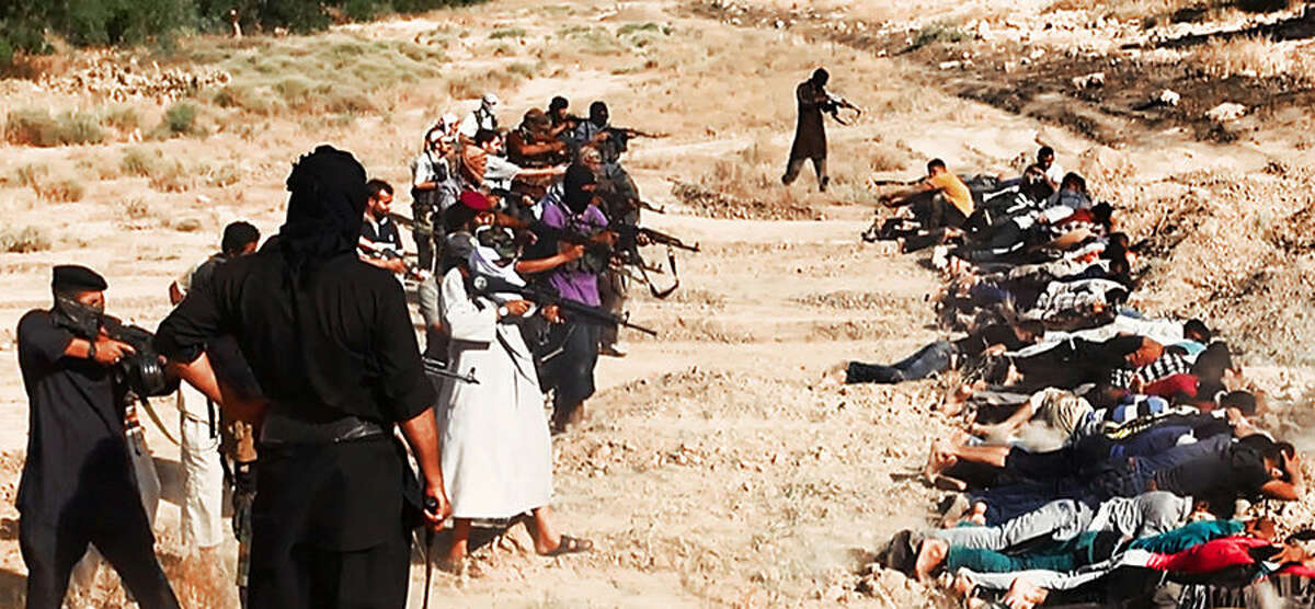 FOR USE AS DESIRED, YEAR END PHOTOS - FILE - This image posted on a militant website on Saturday, June 14, 2014, which has been verified and is consistent with other AP reporting, appears to show militants from the al-Qaida-inspired Islamic State of Iraq and the Levant (ISIL) taking aim at captured Iraqi soldiers wearing plain clothes after taking over a base in Tikrit, Iraq. (AP Photo via militant website, File)