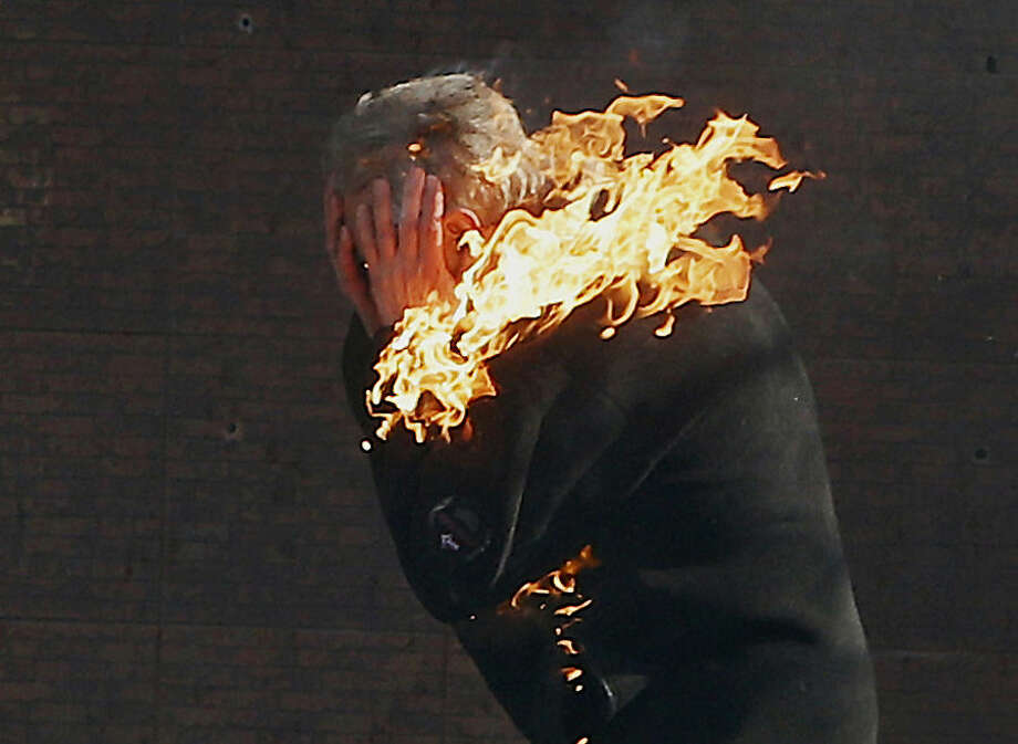 FOR USE AS DESIRED, YEAR END PHOTOS - FILE - An anti-government protester is engulfed in flames during clashes with riot police outside Ukraine's parliament in Kiev, Ukraine, Tuesday, Feb. 18, 2014. (AP Photo/Efrem Lukatsky, File)