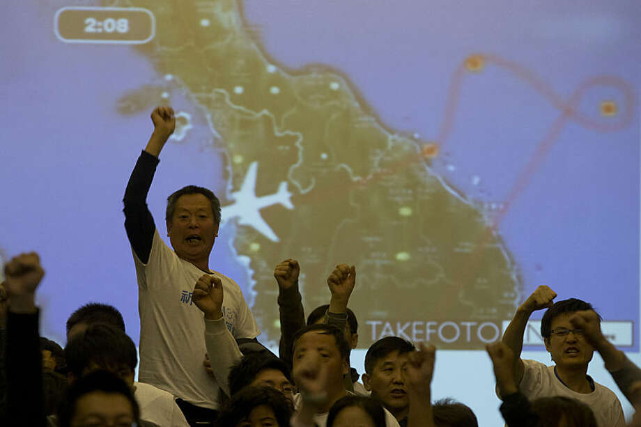 FOR USE AS DESIRED, YEAR END PHOTOS - FILE - Relatives of Chinese passengers aboard the missing Malaysia Airlines, MH370, turn to journalists to shout their demands for answers after Malaysian government representatives left a briefing in Beijing, China, Saturday, March 22, 2014. (AP Photo/Ng Han Guan, File)