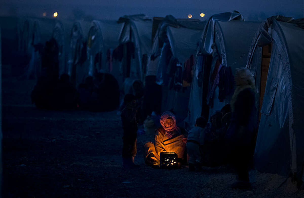FOR USE AS DESIRED, YEAR END PHOTOS - FILE - An elderly Syrian Kurdish refugee woman from the Kobani area, warms up by a fire at a camp in Suruc, on the Turkey-Syria border Monday, Nov. 10, 2014. Kobani, also known as Ayn Arab, and its surrounding areas, has been under assault by extremists of the Islamic State group since mid-September and is being defended by Kurdish fighters. (AP Photo/Vadim Ghirda, File)