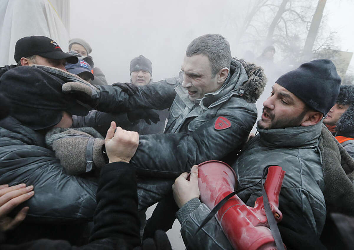 FOR USE AS DESIRED, YEAR END PHOTOS - FILE - Opposition leader and former WBC heavyweight boxing champion Vitali Klitschko, center, is attacked and sprayed with a fire extinguisher as he tries to stop the clashes between police and protesters in central Kiev, Ukraine, Sunday, Jan. 19, 2014. (AP Photo/Efrem Lukatsky, File)