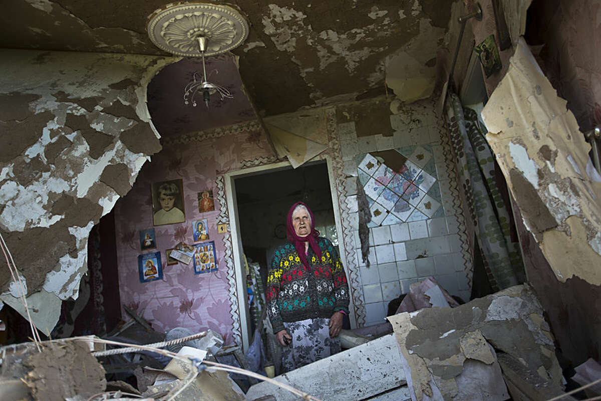 FOR USE AS DESIRED, YEAR END PHOTOS - FILE - Zinaida Patskan, 80, stands in her destroyed house following a shelling from Ukrainian government forces in Semyonovka village near the major highway which links Kharkiv, outside Slovyansk, Ukraine, Thursday, May 22, 2014. (AP Photo/Alexander Zemlianichenko, FILE)