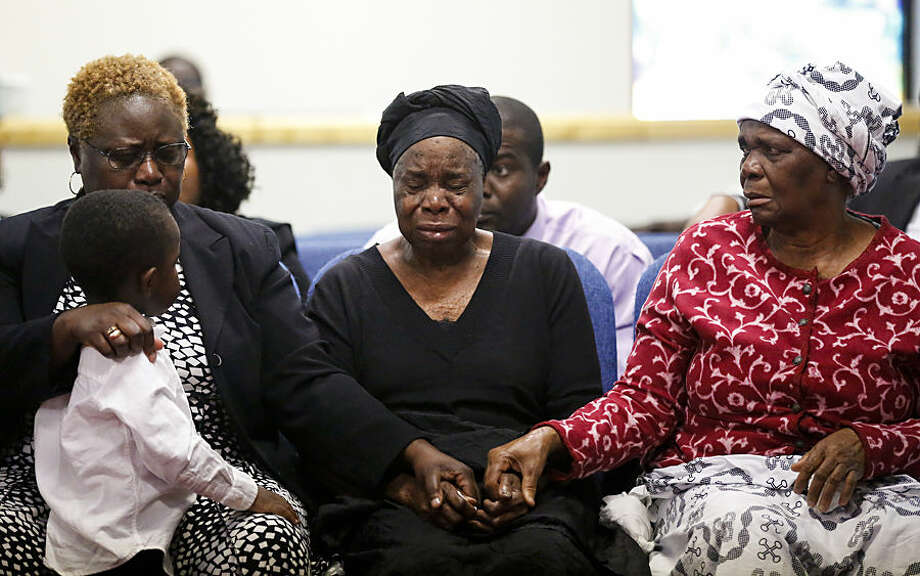 FOR USE AS DESIRED, YEAR END PHOTOS - FILE - Garteh Korkoryah, center, mother of Thomas Eric Duncan, is comforted during a memorial service for her son, Saturday, Oct. 18, 2014, in Salisbury, N.C. Duncan died of Ebola in Dallas on Oct. 8. (AP Photo/Nell Redmond, File)