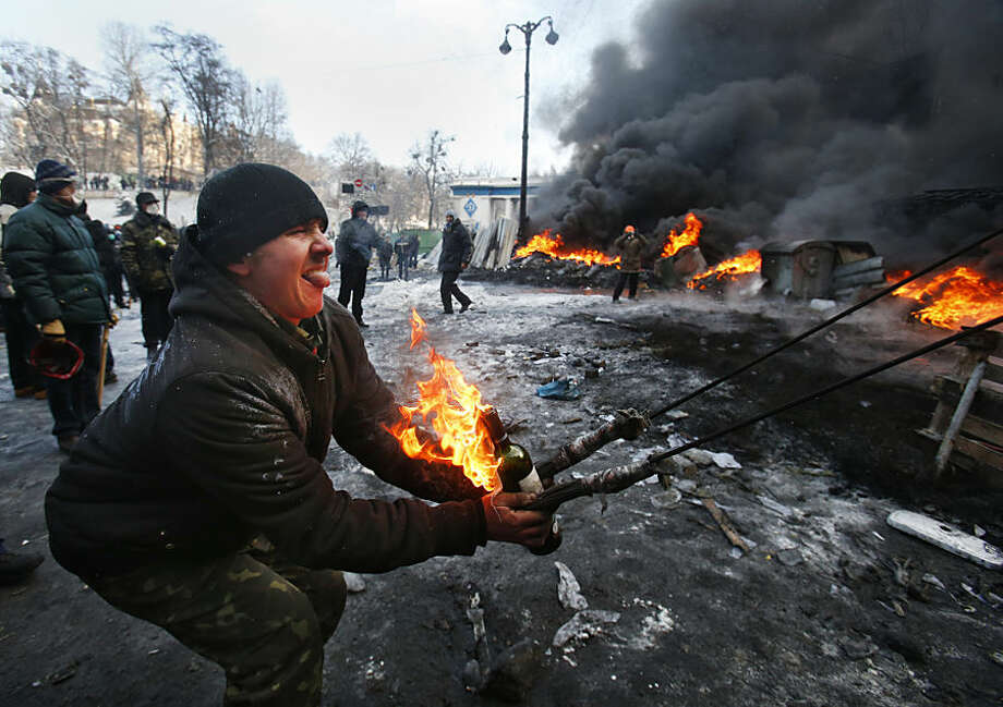 FOR USE AS DESIRED, YEAR END PHOTOS - FILE - Protesters use a large slingshot to hurl a Molotov cocktail at police in central Kiev, Ukraine, Thursday Jan. 23, 2014. (AP Photo/Sergei Grits, File) Photo: Associated Press