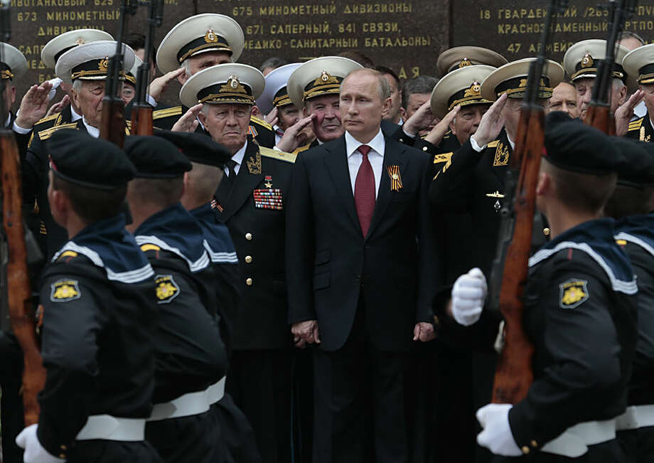 FOR USE AS DESIRED, YEAR END PHOTOS - FILE - Russian President Vladimir Putin attends a parade marking the Victory Day in Sevastopol, Crimea, Friday, May 9, 2014. Putin extolled the return of Crimea to Russia before tens of thousands during his first trip to Black Sea peninsula since its annexation. The triumphant visit was quickly condemned by Ukraine and NATO. (AP Photo / Ivan Sekretarev, File)