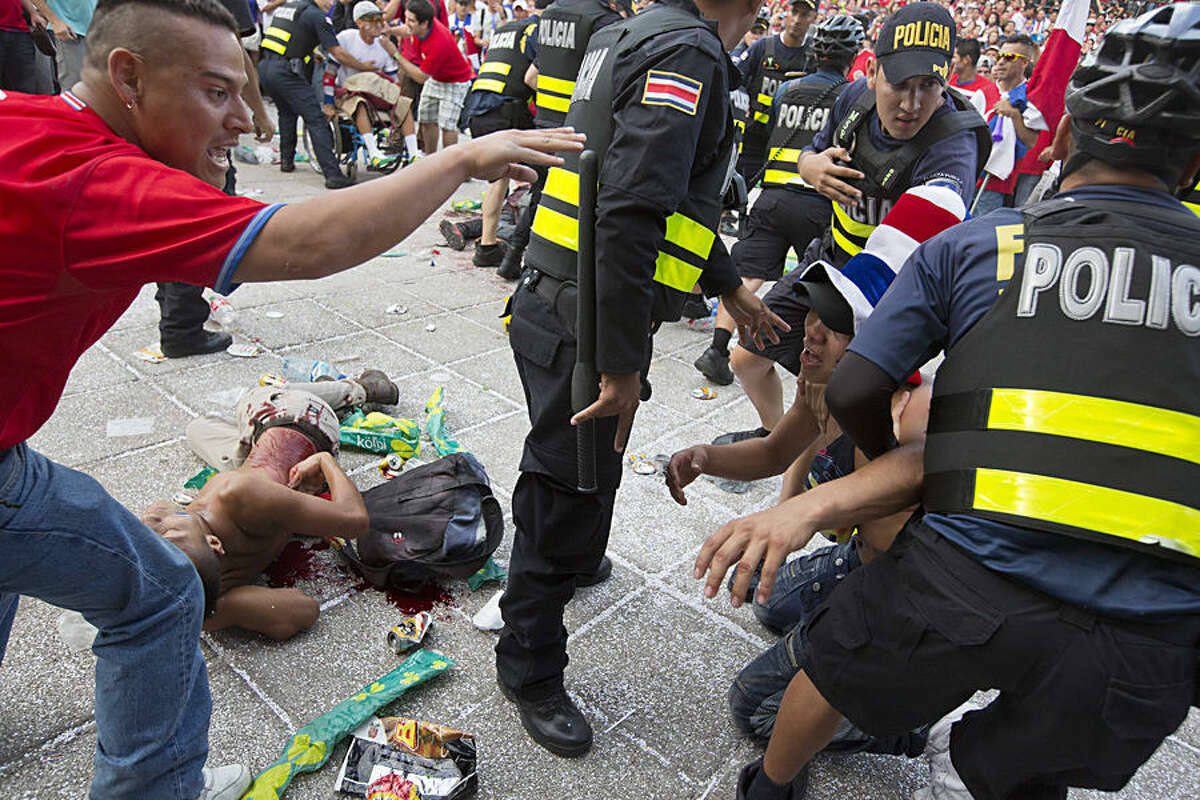 FOR USE AS DESIRED, YEAR END PHOTOS - FILE - A Costa Rica soccer fan is detained by the police while another fan lies on the ground injured with a knife, after a fight broke out during the live telecast of the quarterfinal World Cup match between Costa Rica and The Netherlands, at Democracy square in San Jose, Costa Rica, Saturday, July 5, 2014. Dutch Goalie Tim Krul came on as a substitute in the final minute of extra time and then saved two penalties in a 4-3 shootout victory over Costa Rica on Saturday, giving the Netherlands a spot in the World Cup semifinals. (AP Photo/Esteban Felix, File)